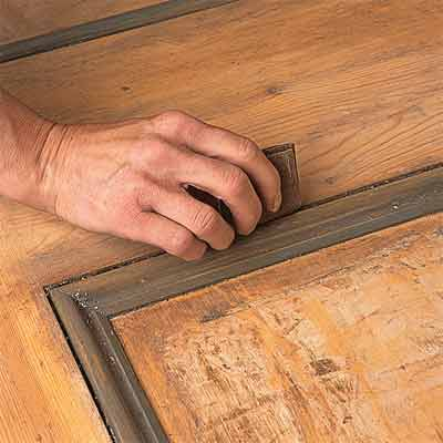 Rubbing down wooden panel door