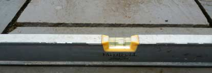 Spirit level showing a 15mm per m fall on patio