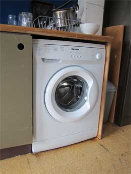 Fitted and connected washing machine pushed back into place
