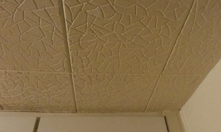 Polystyrene tiles covering bedroom ceiling