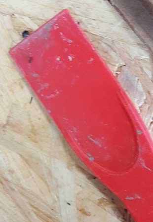 Plastic scraper used to smooth glazing sealant