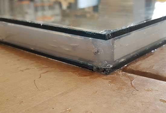 Glazing sealant smoothed using plastic scraper