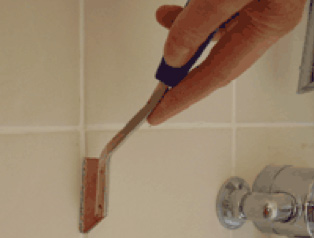 Replacing Grout Between Tiles And Raking Out Tiles For