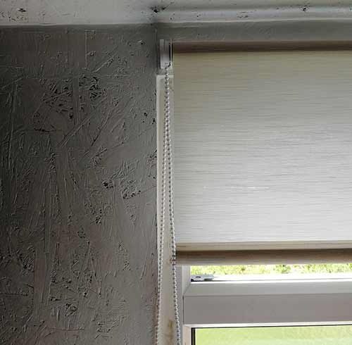 Roller blind covering window reveal