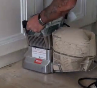 Using an edge sander up to the skirting boards