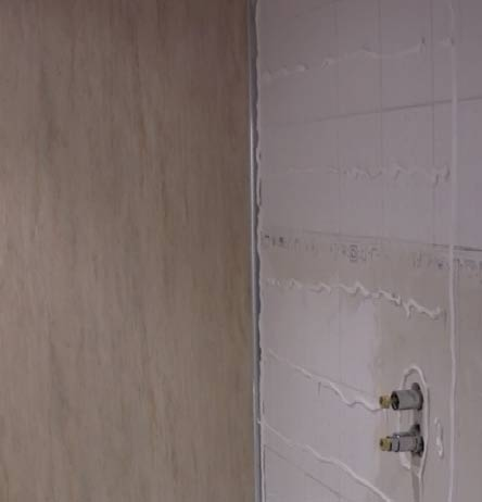 Shower panel adhesive on tiled bathroom wall
