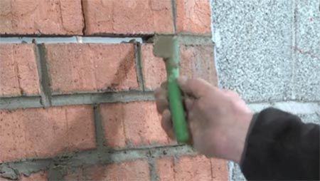 Using a piece of hosepipe to repoint brickwork