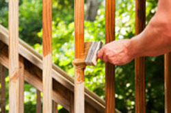 Applying decking stain with a brush to balustrades and stairs