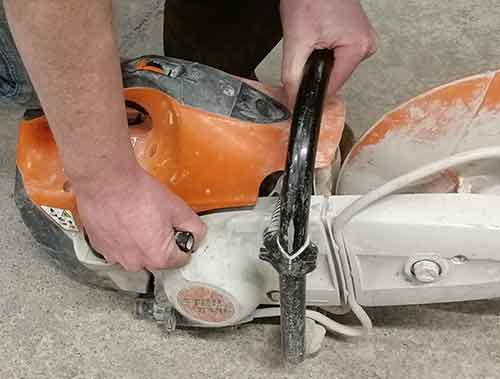 Hold the top handle of the saw and pull start cord