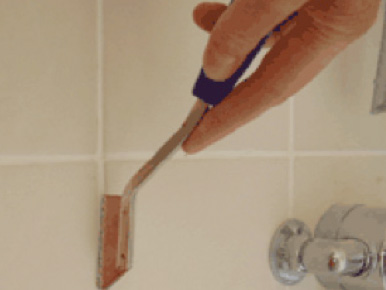 Removing tile grout with a grout rake