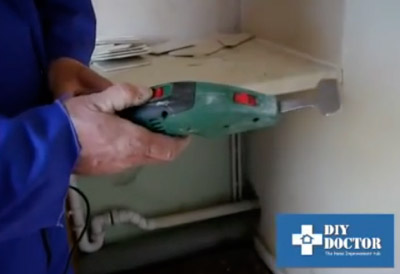 Using a tile scraper to remove ceramic tiles