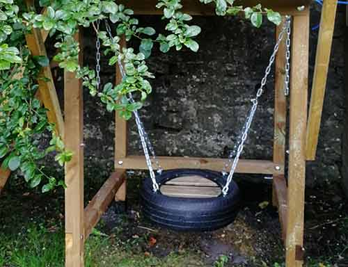 Tyre swing hung beneath playhouse