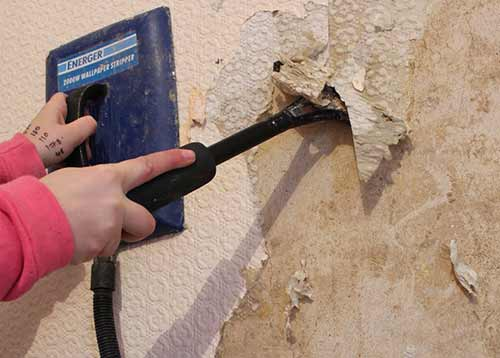 Stripping off wallpaper with stripping knife