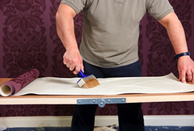 Applying paste to wallpaper on a pasting table