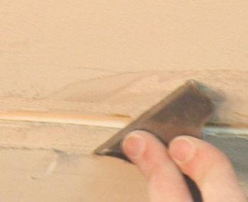 Scraping loose material form ceiling