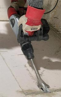 Concrete breaker breaking up concrete floor